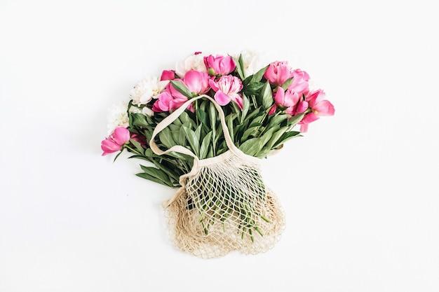 Sac à cordes avec des fleurs de pivoine roses et blanches sur une surface blanche