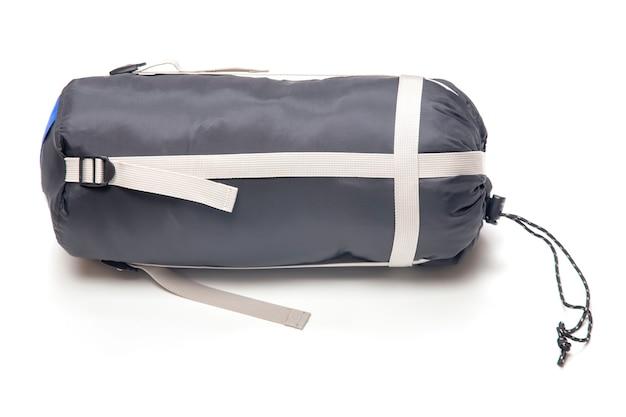 Sac de couchage plié sur un blanc. articles pour le tourisme et le camping