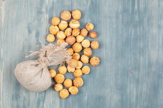 Sac et craquelins ronds avec des graines de sésame sur une surface en bois.