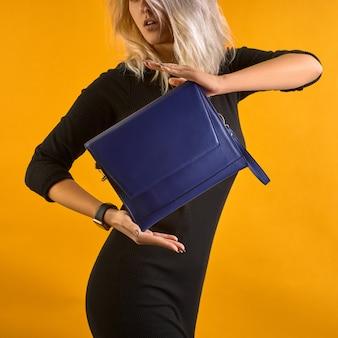 Sac en cuir bleu moderne dans des mains féminines. posant sur fond orange