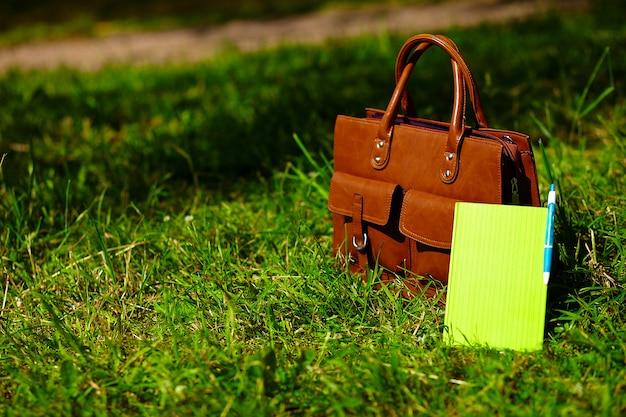 Sac en cuir marron rétro homme et ordinateur portable dans l'herbe d'été coloré lumineux dans le parc