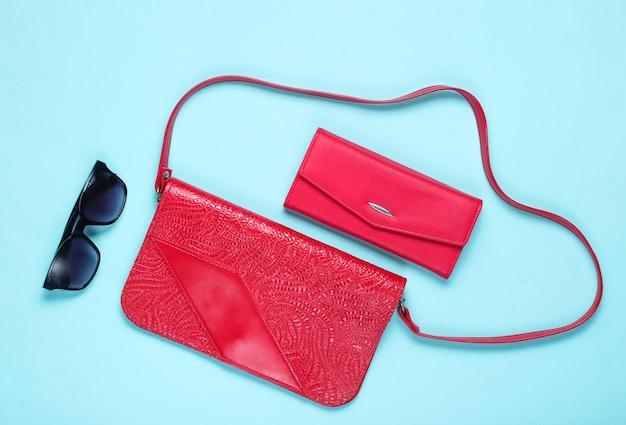 Sac en cuir rouge de style rétro, portefeuille et lunettes de soleil sur bleu, vue de dessus