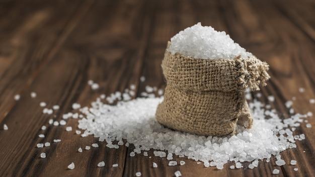 Un sac déchiré de sel émietté sur une table en bois. sel de mer en pierre moulue.