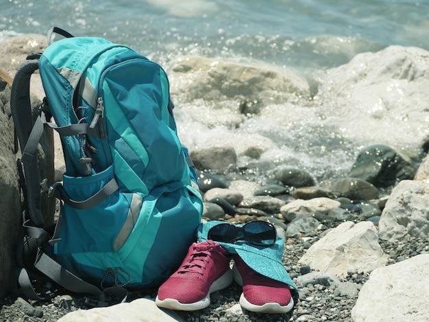 Sac à dos, chaussures de course, casquette et lunettes de soleil sur la plage au fond de l'eau de mer