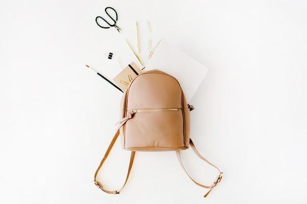 Sac à dos en cuir marron avec des objets d'artiste féminin sur blanc