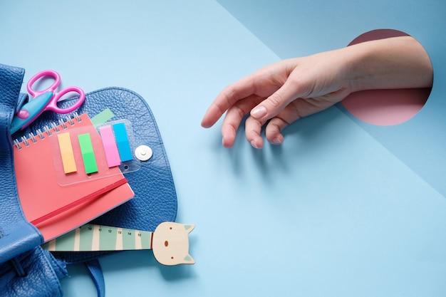 Sac à dos avec différents articles de papeterie colorés sur table.