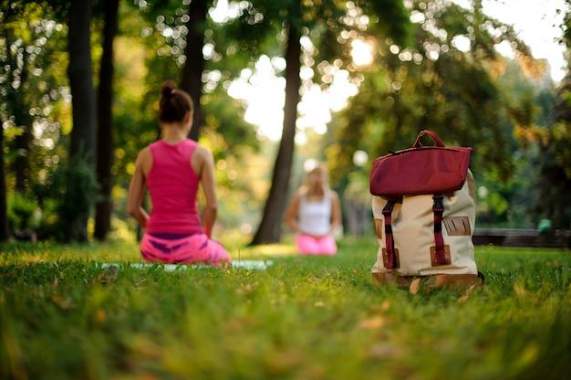 Sac à dos élégant sur l'herbe dans un parc verdoyant le jour d'été contre des cours de yoga