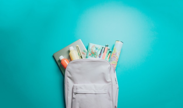 Sac à dos avec des fournitures scolaires colorées sur fond violet. retour à l'école. mise à plat, vue de dessus, espace de copie, design minimal