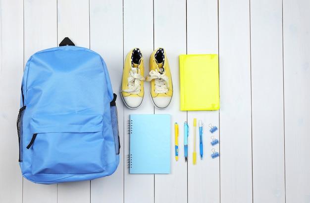 Sac à dos et fournitures scolaires sur une surface en bois, gros plan. vue de dessus.
