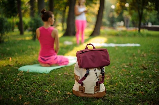 Sac à dos sur l'herbe dans un parc verdoyant le jour d'été contre des cours de yoga