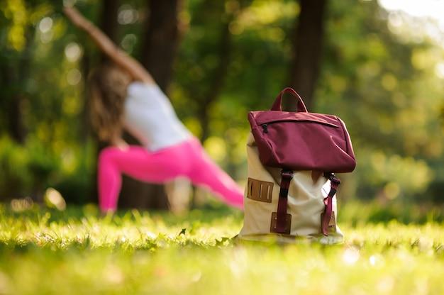 Sac à dos sur l'herbe dans un parc verdoyant le jour d'été contre la femme faisant du yoga