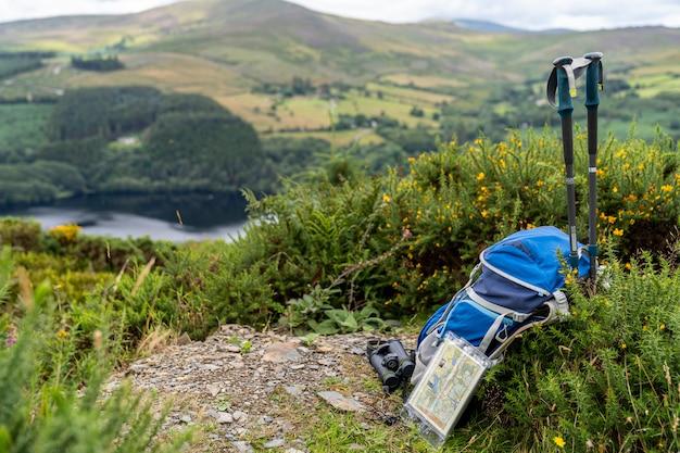 Sac à dos, jumelles, carte et bâtons sur la montagne, mode de vie montagnard en irlande.