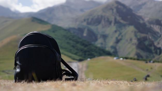 Sac à dos noir sur le fond du mont kazbegi. voyager en géorgie - l'été