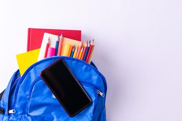Sac à dos avec papeterie colorée différente avec un téléphone intelligent sur fond de tableau blanc