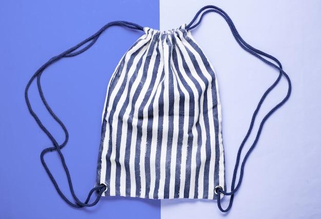 Sac à dos de plage en tissu rayé sur un bleu