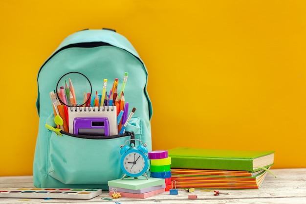 Sac à dos scolaire complet avec différentes fournitures sur fond orange.