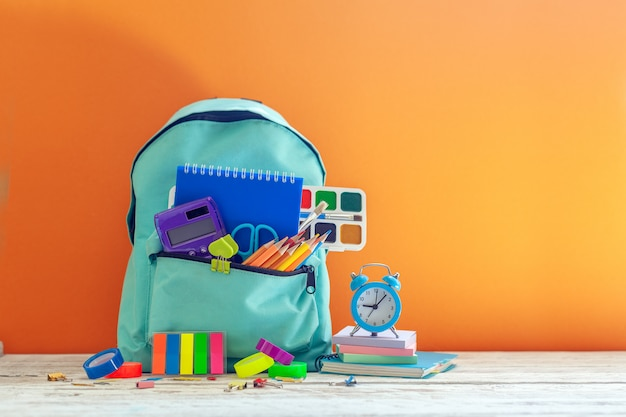 Sac à dos scolaire complet avec différentes fournitures sur orange. concept de retour à l'école.