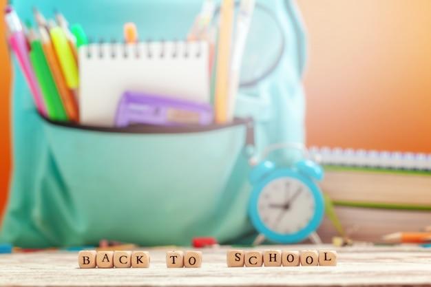 Sac à dos scolaire avec différentes fournitures et réveil sur fond
