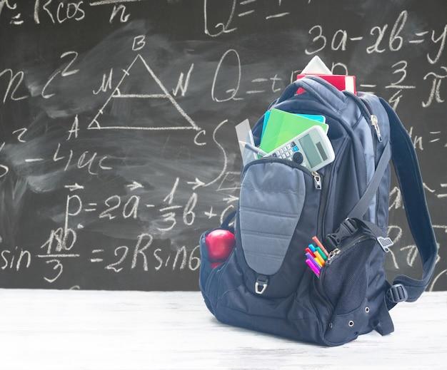 Sac à dos scolaire avec fournitures sur bureau blanc