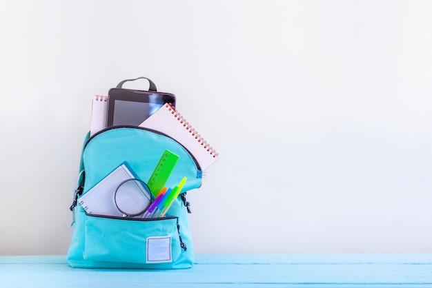 Sac à dos scolaire turquoise avec papeterie sur table.