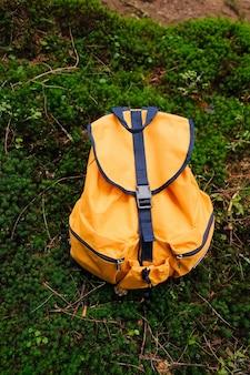 Sac à dos touristique orange dans la forêt sur le temps de mousse verte pour voyager concept