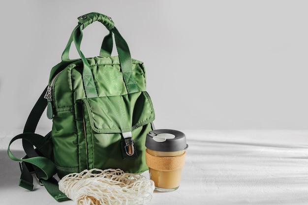 Sac à dos vert avec tasse à café réutilisable. mode de vie durable. zéro déchet, concept sans plastique.