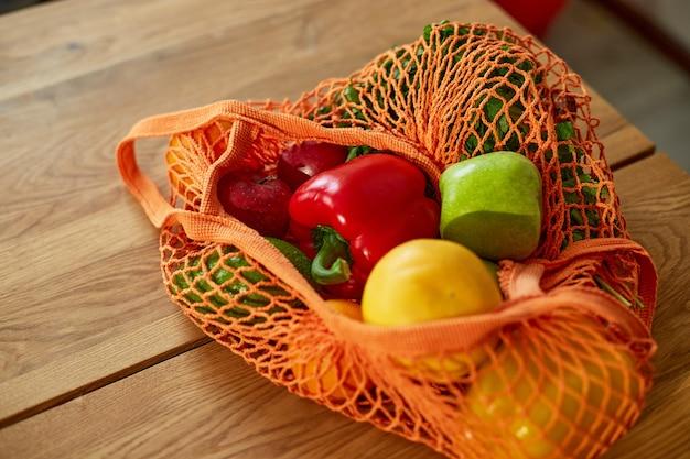 Sac écologique en filet avec des légumes et des fruits végétaliens sains dans la cuisine à la maison