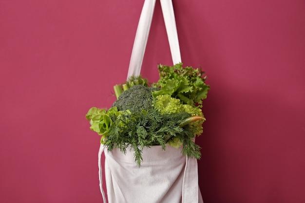 Sac écologique avec des légumes frais accroché au mur