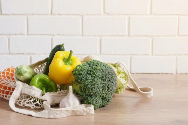 Sac écologique avec de la nourriture sur une table de cuisine en bois