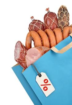 Sac d'épicerie avec des saucisses et de la viande isolé sur fond blanc