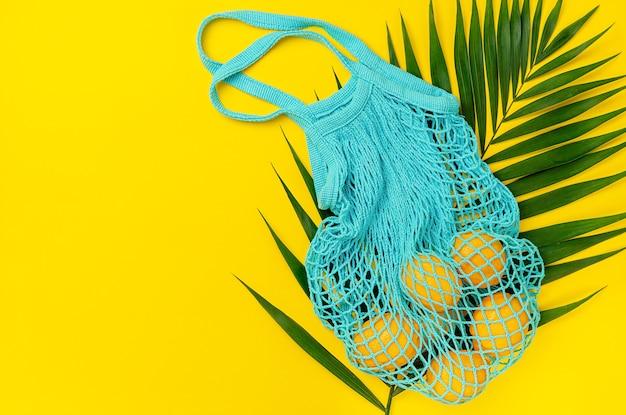 Sac filet bleu avec citrons sur feuille de palmier et fond jaune. directement au-dessus, copiez l'espace.