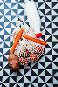 Sac filet avec carottes, lait et tomates avec pommes de terre sur un plancher. vue ci-dessus