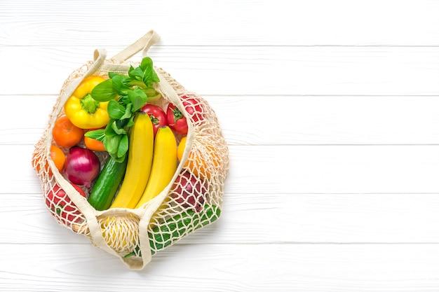 Sac en filet écologique complet de différents aliments de santé - poivron, tomates, bananes, citron, vert, mandarine, concombre, oignons sur fond en bois blanc