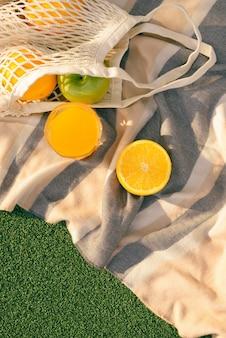 Sac filet de fruits sur le plaid dans le domaine
