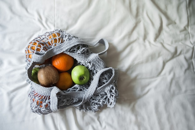 Sac en filet gris avec gros plan d'oranges jaunes et espace de copie. sac écologique fait main sur textiles