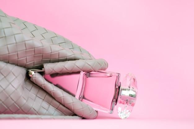 Sac sur fond rose. une bouteille de parfum tombe du sac d'une femme