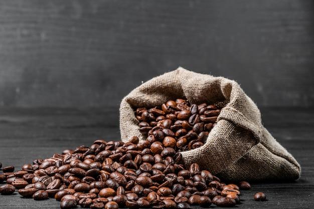 Sac avec des grains de café dispersés isolés sur fond noir