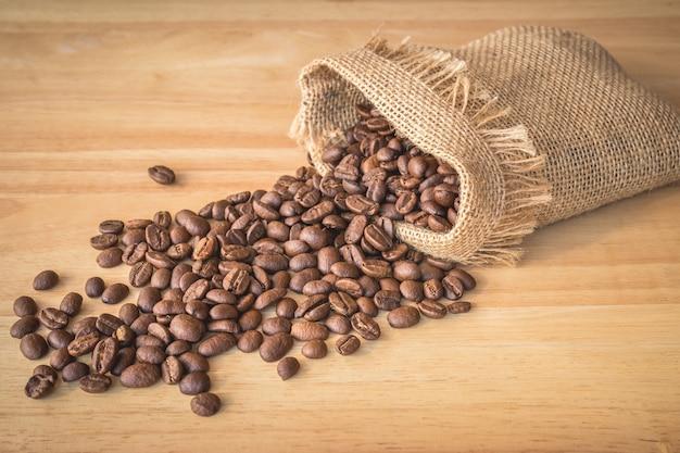 Sac de grains de café sur fond de bois