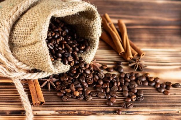 Sac de jute grossier avec des grains de café saupoudrés sur une table en bois brûlé avec des bâtons de cannelle et des étoiles d'anis.