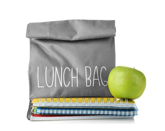 Sac à lunch avec de la nourriture pour écolier et cahiers sur blanc