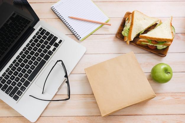 Sac à lunch avec sandwich et fruits dans la table de bureau
