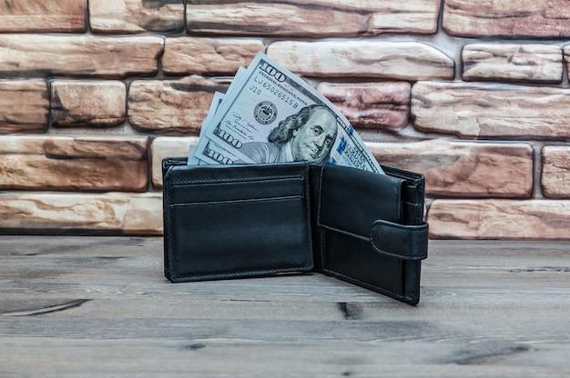 Un sac à main avec des factures de cent dollars sur une table en bois sur un fond de mur de brique rouge.