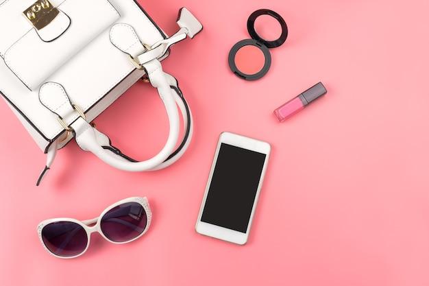 Sac à main femme avec maquillage et accessoires isolés sur fond rose