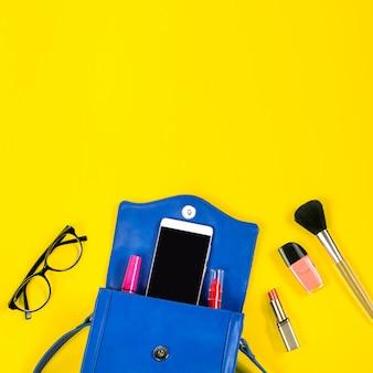 Sac à main femme, produits de beauté, smartphone, lunettes sur fond jaune vif, vue de dessus