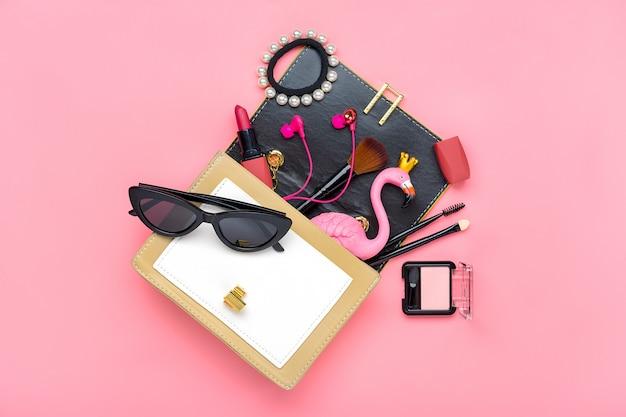 Sac à main jaune avec accessoires femme sur table rose