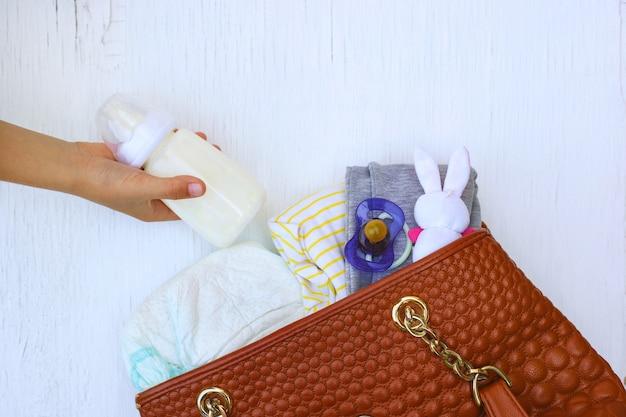 Sac à main de mère avec des articles pour s'occuper de l'enfant