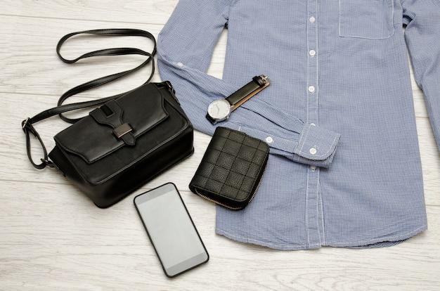 Sac à main noir, téléphone portable, sac à main et une montre dans la chemise bleue. concept de mode. vue de dessus