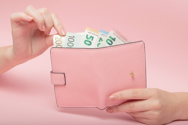 Sac à main rose et billets en euros dans les mains des femmes