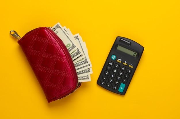 Sac à main rouge avec des billets de cent dollars et une calculatrice sur jaune. compter le coût des achats.
