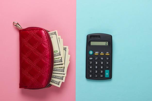 Sac à main rouge avec des billets de cent dollars et une calculatrice sur un pastel bleu-rose.